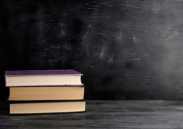 Vier gesloten boeken met gele bladen op een schoolbord