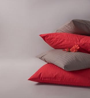 Vier gestapelde kussens met rode bloem tegen de witte achtergrond.