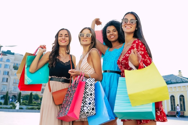 Vier geweldige vrouwen in zomeroutfits poseren op straat in het stadscentrum, lachend van vreugde en tonen hun aankopen aan de camera