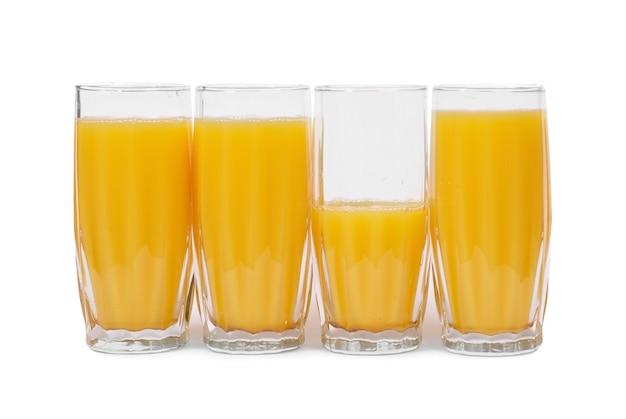 Vier glazen met jus d'orange op wit wordt geïsoleerd