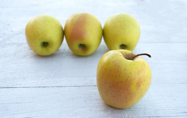 Vier gouden appels op een witte houten achtergrond