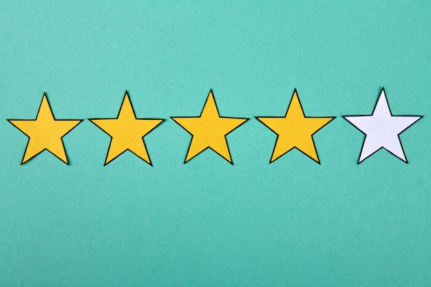 Vier gouden sterren van vijf op turkooizen achtergrond