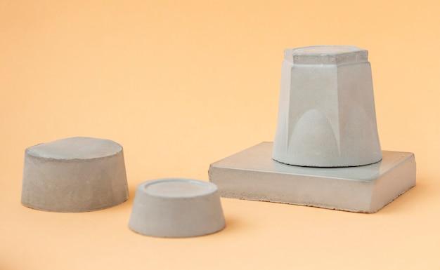 Vier grijze podia met een geometrische betonnen figuur.