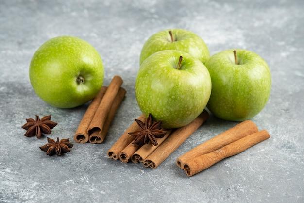 Vier groene appel en kaneelstokjes op marmeren tafel.