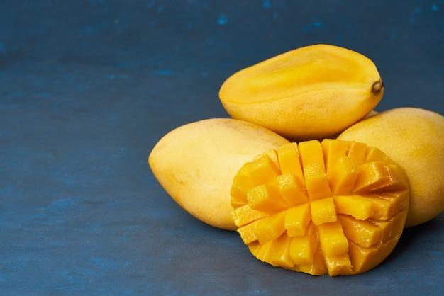 Vier hele mangovruchten op donkerblauwe tafel en in plakjes gesneden. grote sappige rijpe gele vruchten