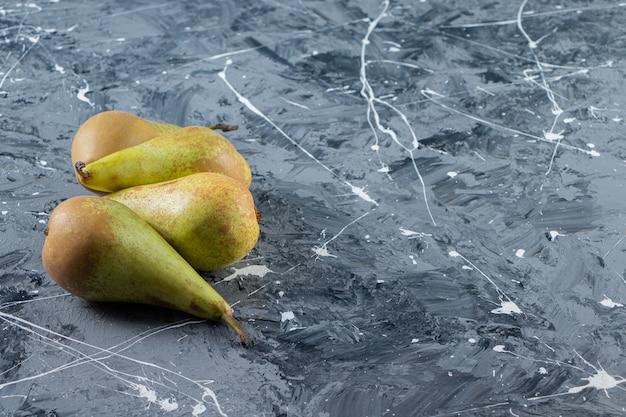 Vier hele verse peren op een marmeren tafel.