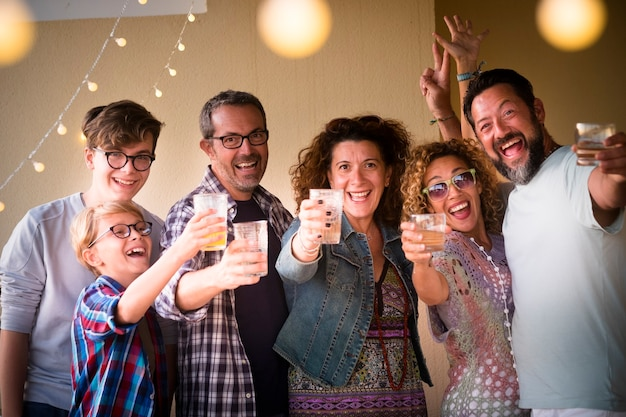 Vier het concept van mensen met verschillende leeftijden, volwassenen en jongeren die allemaal samen proosten, veel plezier hebben en veel lachen - van kind tot tiener tot volwassen mannen en vrouwen in een feestavond