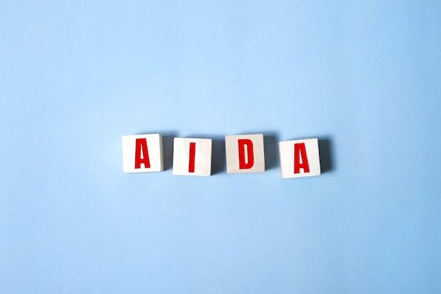 Vier houten kubussen met de letters aida voor aandacht, bewustzijn, belang, verlangen actie. marketing bedrijfsconcept.