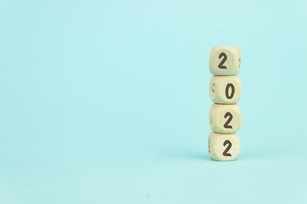 Vier houten speelgoedkubussen verticaal gerangschikt op blauwe achtergrond met tekst 2022, bedrijfsgroei en managementconcept.