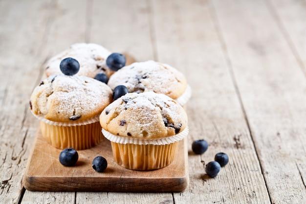 Vier huisgemaakte verse muffins met bosbessen op rustieke houten tafel achtergrond.