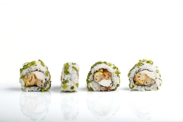 Vier japanse broodjes van makisushi op een rij met roomkaas en ui die op wit wordt geïsoleerd