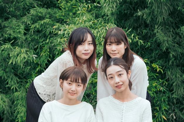 Vier japanse vrouwen die buiten naast elkaar naar de camera kijken