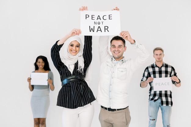 Vier jonge activisten van verschillende nationaliteiten houden slogans voor vrede, geen oorlog en bescherming van de aarde