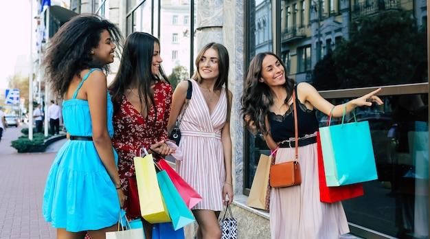 Vier jonge en mooie vrouwen in zomerjurken lopen samen door de straten van de stad, sjouwen met boodschappentassen en kletsen levendig