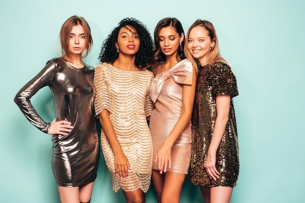 Vier jonge internationale mooie brunette vrouwen in trendy glanzende zomerjurk.