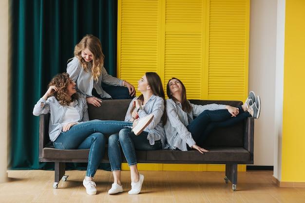 Vier jonge meisjes in gestreepte shirts, jeans en sneakers die zich voordeed op de bank