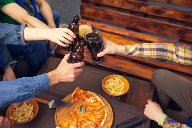 Vier jonge mensen, sportieve fans ontmoeten elkaar in de bar. concept van vriendschap, vrijetijdsbesteding