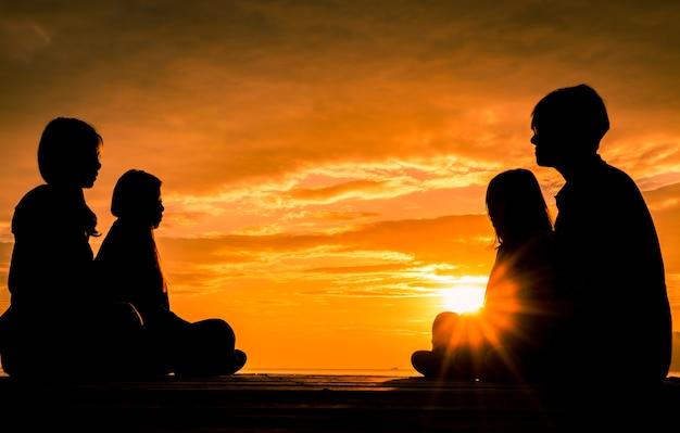 Vier jonge mensen zitten op houten pier bij zonsopgang