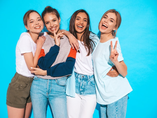 Vier jonge mooie glimlachende hipster meisjes in trendy zomerkleren. sexy onbezorgde vrouwen die dichtbij blauwe muur in studio stellen. positieve modellen die plezier hebben en knuffelen