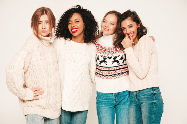Vier jonge mooie lachende hipstermeisjes in trendy wintertruien. positieve modellen die plezier hebben en knuffelen