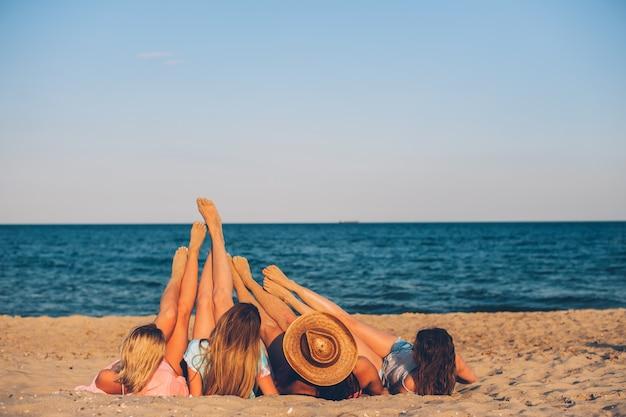 Vier jonge mooie meisjeshoeden zitten op het strand