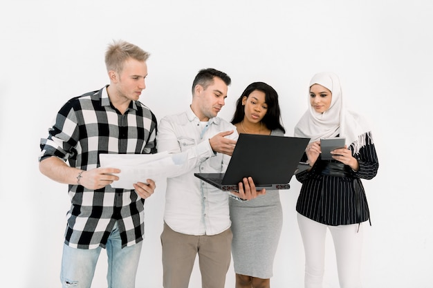 Vier jonge multi-etnische mensen, afrikaanse en moslimmeisjes, twee blanke mannen, met papieren en verschillende gadgets
