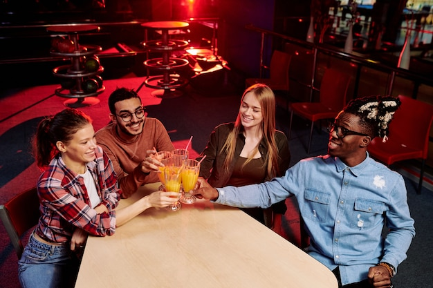 Vier jonge multi-etnische vrienden in vrijetijdskleding rammelende met glazen sinaasappelsap terwijl ze de overwinning van hun bowlingteam vieren