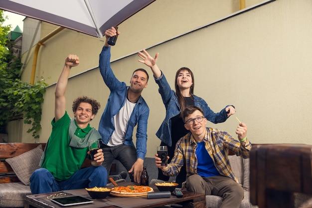 Vier jonge sportieve fans die elkaar ontmoeten in de bar en bier drinken concept van vriendschap