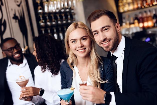 Vier jongens en meisjes drinken cocktails in een bar.