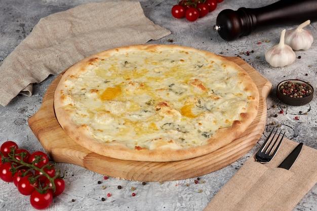 Vier kaas pizza op een houten bord, grijze achtergrond