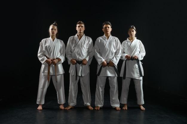 Vier karateka's in witte kimono, groepstraining. karatevechters op training, vechtsporten, vechtwedstrijden