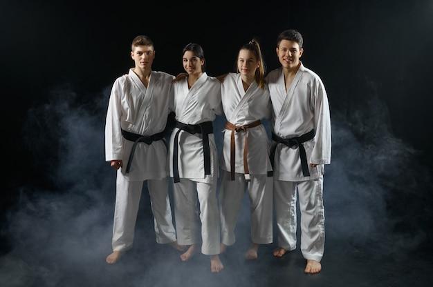 Vier karatestrijders in witte kimono vormen in een knuffel, groepstraining. karatekas over training, vechtsporten, vechtwedstrijden