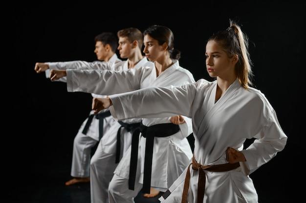 Vier karatevechters poseren in witte kimono, groepstraining. karatekas over training, vechtsporten, vechtwedstrijden