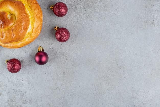 Vier kerstboomversieringen opgesteld naast een broodje op een marmeren oppervlak