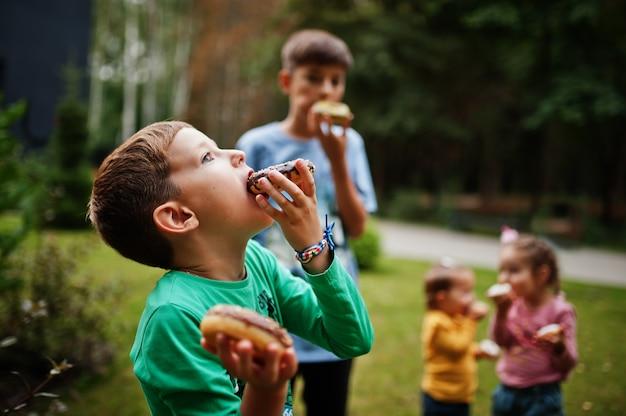 Vier kinderen met donuts op de avondtuin. lekker lekker donut eten.