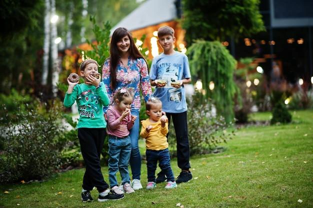 Vier kinderen met moeder eten donuts in de avondtuin. lekker lekker donut eten.