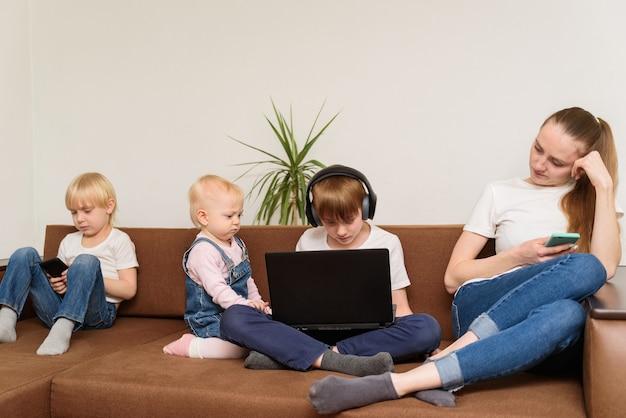 Vier kinderen van verschillende leeftijden die op bank met telefoons en laptop zitten