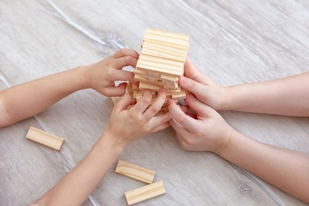Vier kinderhanden verzamelen een toren van houten blokken op de vloer. detailopname. gezinsbordspellen