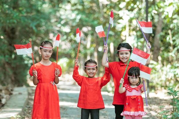 Vier kleine meisjes glimlachen als ze staan met rode en witte attributen