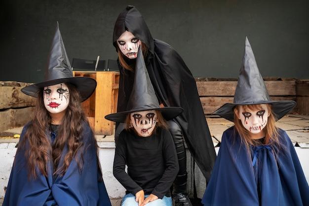 Vier kleine meisjes in carnavalskostuums van heksen en zombies