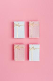 Vier kleine roze en witte geschenkdozen. concept of wenskaart minimale stijl. romantiek bovenaanzicht