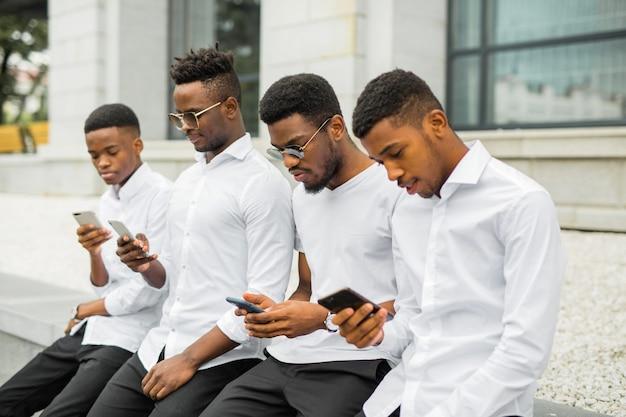 Vier knappe jonge afrikaanse mannen in witte shirts met telefoons in hun handen