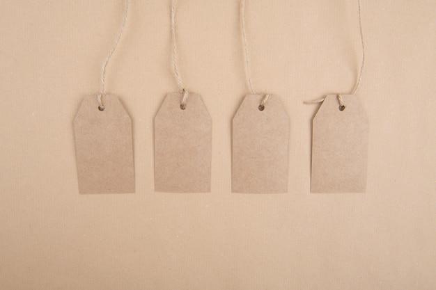 Vier labels van gerecycled kraftpapier die aan een touw op kraftpapier hangen. plat leggen