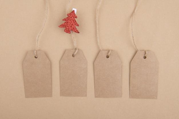 Vier labels van gerecycled kraftpapier die met een wasknijper aan een touw hangen met een rode kerstboom op kraftpapier. plat leggen