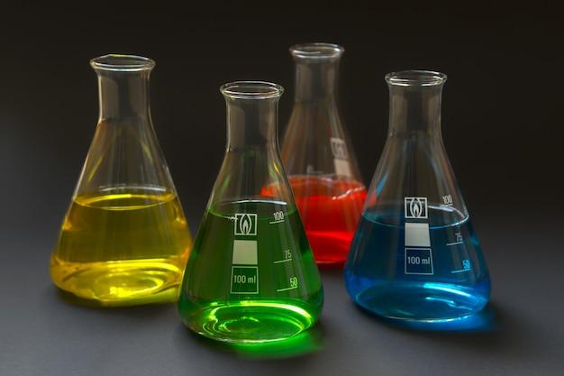 Vier laboratoriumflessen met kleurrijke die vloeistoffen op donkere achtergrond worden geïsoleerd.