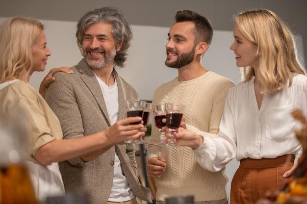 Vier lachende familieleden in vrijetijdskleding rammelend met glazen rode wijn en kijken naar gelukkige rijpe blonde vrouw tijdens de viering