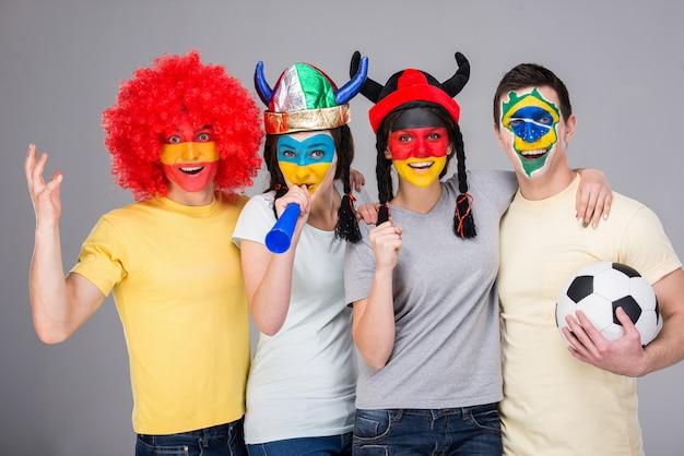Vier lachende fans met nationale vlaggen geschilderd op de gezichten.