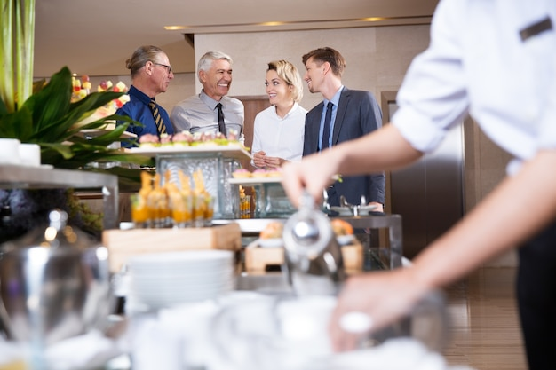 Vier lachende mensen bij buffet table