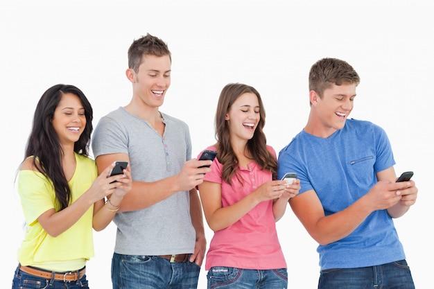 Vier lachende vrienden die teksten op hun telefoons verzenden