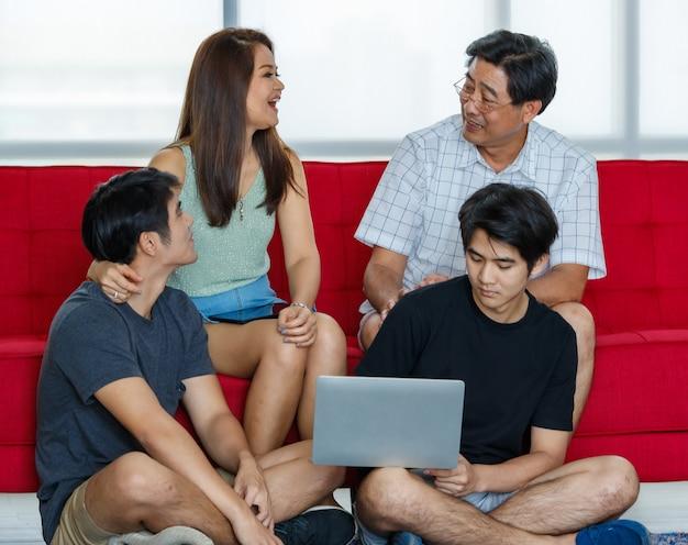 Vier leden aziatische familie bestaande uit ouders, twee volwassen zonen die graag samen tijd doorbrengen tijdens vakanties, met behulp van een laptop in een comfortabele woonkamer thuis. presenteren van moderne technologie concept.